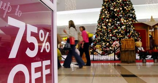 Shoppers move past many stores brimming with lots of sales, luring them in for big savings at Woodland Mall. (T.J. Hamilton | The Grand Rapids Press)